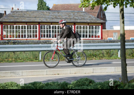 Commuter riding a bicycle - Stock Image