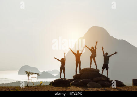 Group of four people stands on the top of mountain in winner pose. Team or teamwork success concept. Space for text - Stock Image