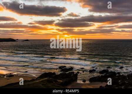 Sunset over a stormy Fistral Beach with surfers, Newquay, Cornwall, UK - Stock Image