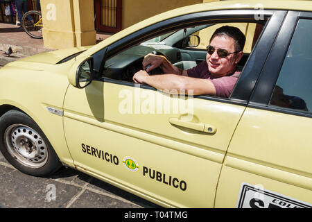 Cartagena Colombia Old Walled City Center centre Centro taxi taxis cab cabs driver driving working Hispanic resident residents yellow - Stock Image