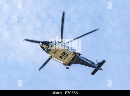 Underside of low flying Kent, Surrey & Sussex air ambulance helicopter (G-KSST) in West Sussex, England, UK. Aircraft is AgustaWestland AW169. - Stock Image