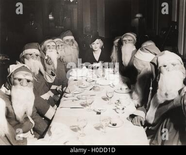Woman lunching with twelve Santa Clauses - Stock Image