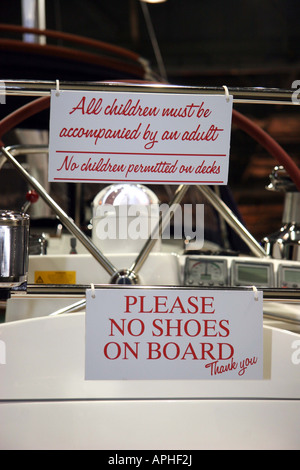 warning sign at the london boat show, please no shoes on board, thank you and all children must be accompained by - Stock Image