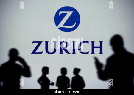 The Zurich Insurance logo is seen on an LED screen in the background while a silhouetted person uses a smartphone (Editorial use only) - Stock Image