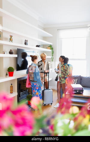 Young women friends with suitcases talking in house rental - Stock Image
