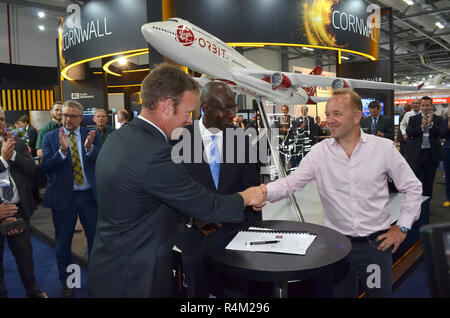 Leader of Cornwall Council Adam Paynter (left) shakes hands with Patrick McCall, chairman of Virgin Orbit, with UK Science Minister Sam Gyimah - Stock Image