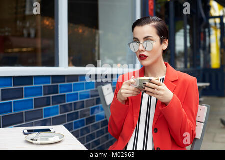 Woman in red jacket sitting outside a cafe, waist up - Stock Image