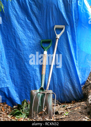 Garden fork and spade leaning on blue tarpaulin - Stock Image