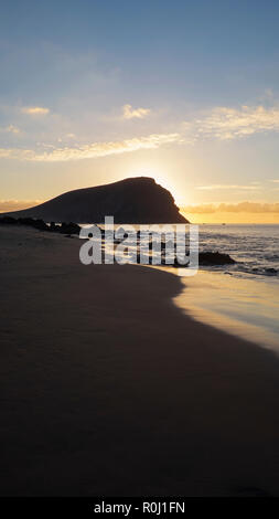 Sunrise over Montana Roja, an unusual, stratovolcanic cone and La Tejita beach, one of the longest, natural beaches in Tenerife, Canary Islands, Spain - Stock Image