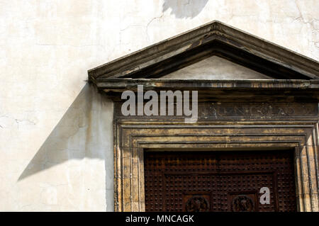 sunlilt corner of a medieval wooden door frame and cpital in florence italy with sharp corner shadow - Stock Image