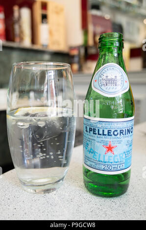 S.Pelligrino Sparkling mineral water bottle and glass with ice and lemon in an Italian Cafe - Stock Image