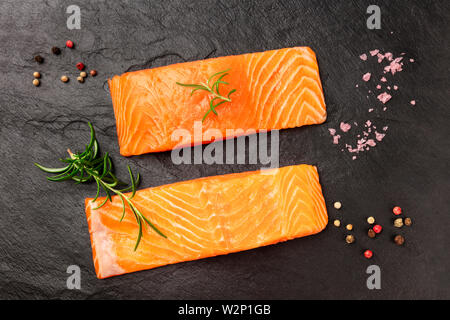 Two slices of raw salmon with rosemary, salt and peppercorns on black - Stock Image