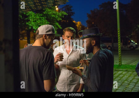 Group of customers at food truck drinking and eating - Stock Image
