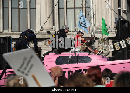 One of the last remaining Extinction Rebellion demonstrators, who glued himself to the mast of 'Tell the truth' boat, about to be detached by police in Oxford Circus, London. - Stock Image