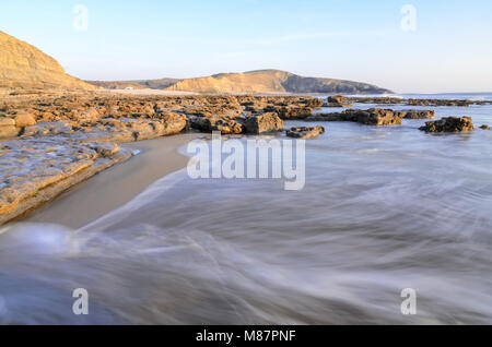 Waves along the rocky shoreline of Dunraven Bay near Southerndown in South Wales, England - Stock Image