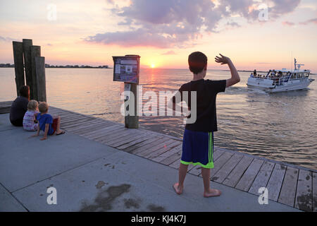Boy waving to water taxi, Fair Harbor, Fire Island, NY, USA - Stock Image