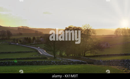 UK Weather: spectacular sunset along the A515 road between Buxton & Ashbourne in the Peak District National - Stock Image