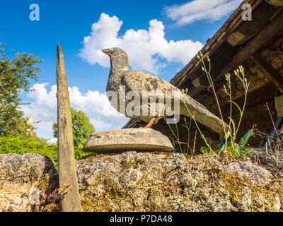 Carved stone pigeon on garden wall, France. - Stock Image