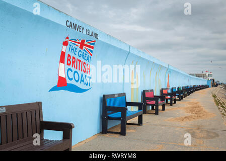 Coast UK seaside, view of benches along the blue sea wall on Canvey Island seafront, Essex, England, UK - Stock Image