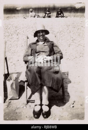 A woman called June looking very comfortable and organised in a deckchair on an unidentified beach. - Stock Image