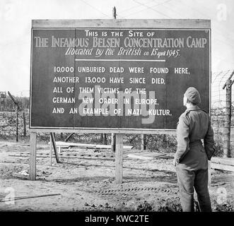 British soldier stands by a sign posted at the site of the Belsen Concentration Camp, 1945. Sign reads: 10,000 unburied - Stock Image