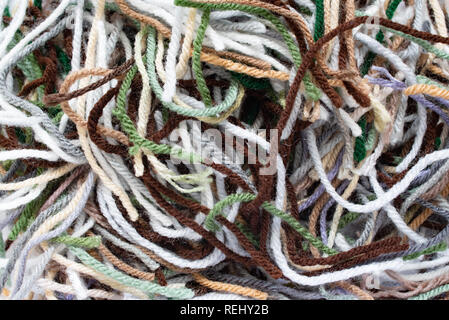 A pile of acrylic yarn pieces in many colors left over from crocheting an afghan. - Stock Image