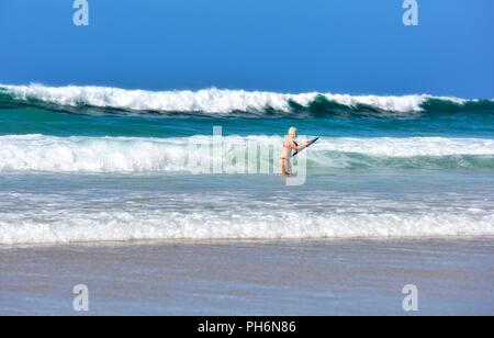 Blond female body boarding in the sea,Riviere Towans beach,Riviere Towans beach, Phillack, Hayle,cornwall,England,UK - Stock Image