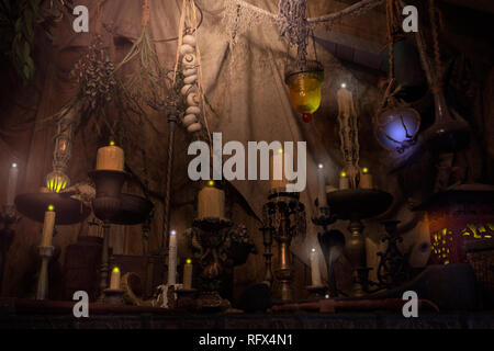 A  pirate's lair with glowing candles and mysterious artifacts are one of the sights to see upon exiting the Pirates of the Caribbean ride. - Stock Image