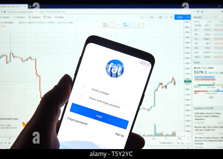 MONTREAL, CANADA - APRIL 26, 2019: Fatbtc cryptocurrency exchange logo and application on Android Samsung Galaxy s9 Plus screen in a hand over a lapto - Stock Image