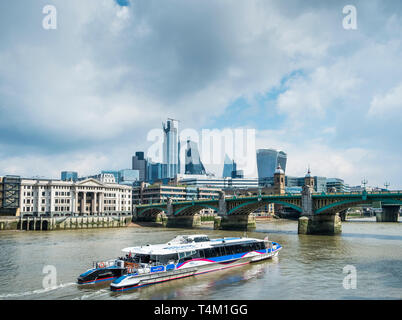 A Thames Clipper River Boat on the River Thames approaching Southwark Bridge in London. - Stock Image