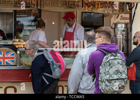 people queuing for food at a fast food van at a festival - Stock Image