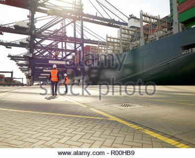 Dock workers beside cargo ship at Port of Felixstowe, England - Stock Image