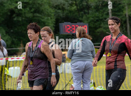 Muddied runners at the finish of a Suffolk mud run - Stock Image