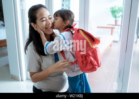 little girl with school uniform kiss her mom at home before going to school - Stock Image