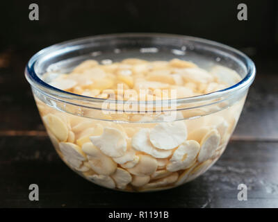 Dried split fava beans being soaked in water. - Stock Image