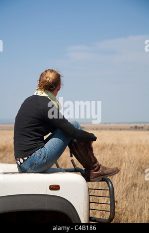Tanzania, Serengeti. A woman looks out over the Serengeti plains from the bonnet of her Land Rover. MR. - Stock Image