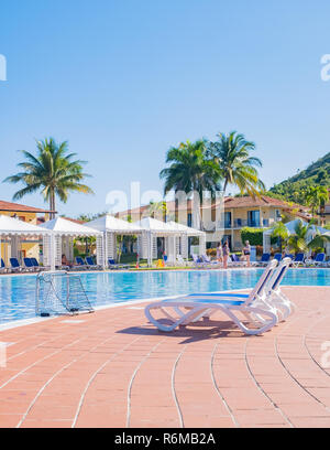 Two blue lounge chars beside a pristine beautiful swimming pool at a resort in Cuba, - Stock Image