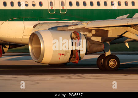 Closeup of a CFM56 turbofan jet engine nacelle on an Airbus A320 airliner while landing with thrust reversers actuated. Left main wheels also visible. - Stock Image