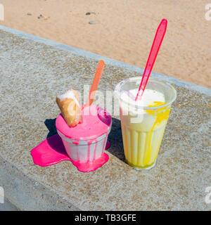 Melting ice cream on sea walloverlooking beach. UK - Stock Image