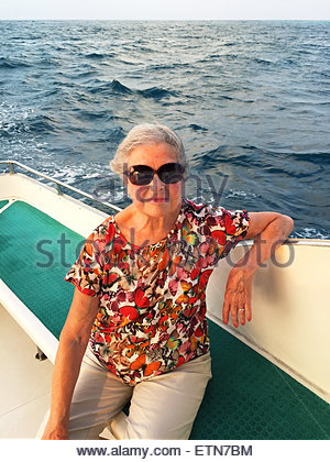 Portrait of a senior woman sitting on boat, Maldives - Stock Image