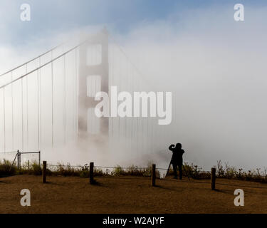 The silhouette of unidentified photographer shooting the Golden Gate Bridge with a camera and a cell phone on a foggy morning, viewed from Battery Spe - Stock Image