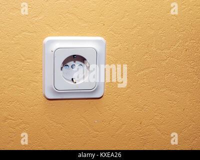 Indoor electric power line socket on yellow wall - Stock Image