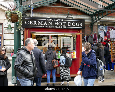 Stall in a busy and crowded Covent Garden selling German Hot Dogs - Stock Image
