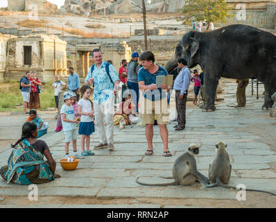 Tourists  outside the Virupaksha temple in Hampi in India - Stock Image
