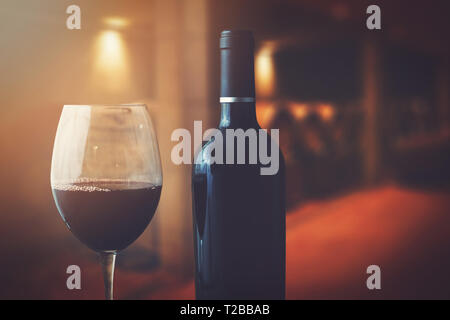 wine bottle and glass in wine cellar - Stock Image