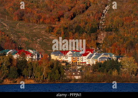 North America, Canada, Quebec, St- Jovite, picturesque lakeside resort with colorful rooftops and fa?ades, in Laurentian Mountains set amid backdrop o - Stock Image