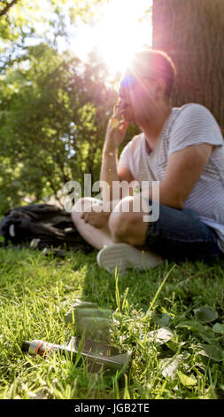 Young man smoking cigarette with electronic cigarette on foreground - Stock Image