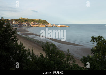 Scarborough beach with Scarborough Castle, harbour and lighthouse in distance. unsharpened - Stock Image