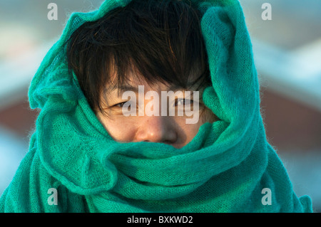 Korean woman wrapped up to stay warm in the winter. - Stock Image