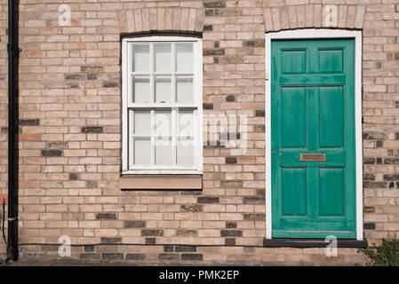Green pastel vintage front door on a restored brick wall of a Georgian house residential building with white wooden sash window - Stock Image